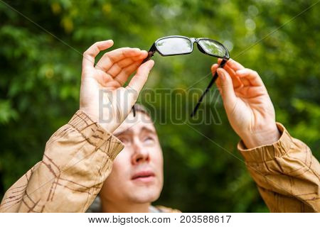 Photo of man holding glasses over head against background of trees