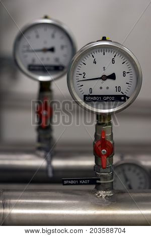 Industrial gauges with valves and pipes in industrial process.