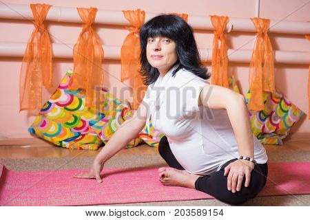Pregnancy Yoga and Fitness concept. Healthy maternity lifestyle concept. 40 week pregnant middle aged caucasian woman doing yoga exercises.