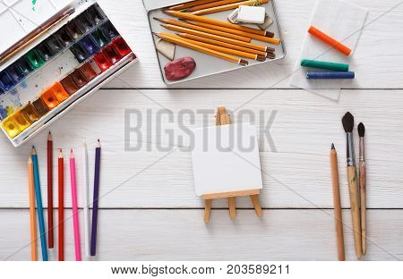 Artist workspace. Drawing tools, stationary supplies, workplace of artist. Watercolor paints and blank paper on white wooden desk, top view, flat lay, copy space