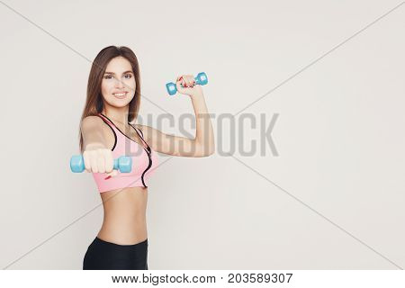 Fitness model woman with dumbbells on white studio background. Young girl in fitwear with sport equipment. Bodybuilding, healthy lifestyle concept