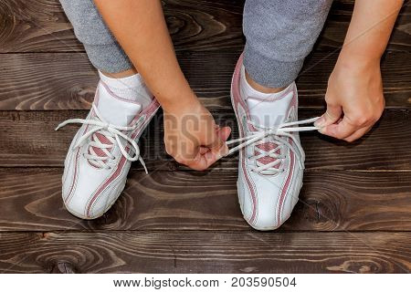 Tying Shoe laces girl sitting on the wooden floor. White sneakers on a dark wooden background.The view from the top.
