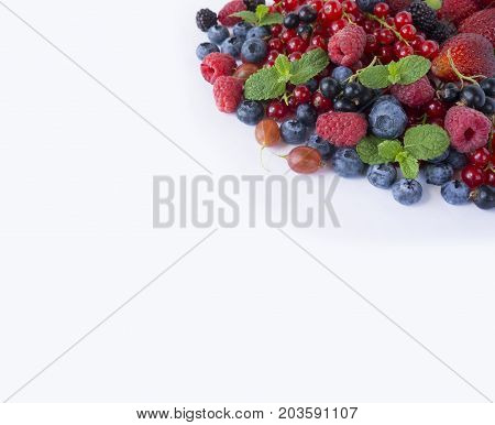 Various fresh summer berries on white background. Ripe raspberries blueberries blackberries gooseberries black currants and red currants mint. Berries with copy space for text. Background berries. Top view.