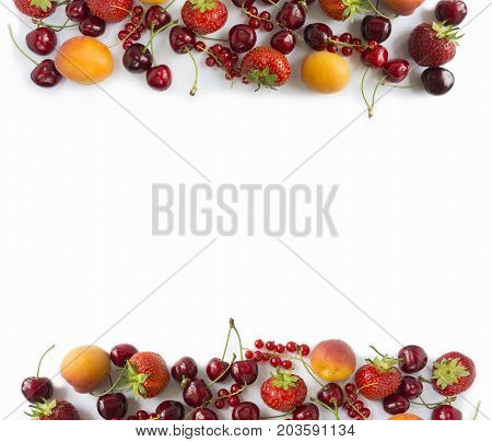 Ripe strawberries redcurrants apricots and cherries on white background. Various fresh summer berries. Top view. Berries at border of image with copy space for text. Background berries.