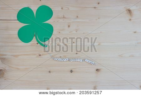The german words for Happy New Year and a cloverleaf on a cord on wood