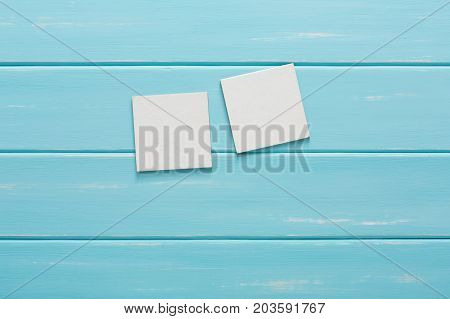White blank cards on blue wooden background. Creative reminder, small sheets of paper, bright memo backdrop