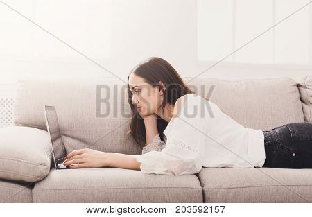 Girl working on laptop at home laying on comfortable biege sofa.