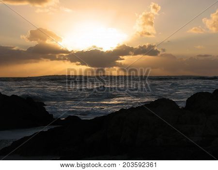 A SILHOUETTE IN THE FORE GROUND, WITH THE GOLDEN RED RAYS OF THE SUN, SETTING IN THE BACK GROUND