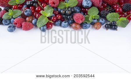 Various fresh summer berries on white background. Ripe raspberries blueberries blackberries gooseberries black currants and red currants mint. Berries at border of image with copy space for text. Background berries. Top view.