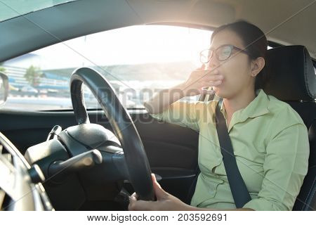 Tired Sleepy Asian glasses Girl yawning Business woman driving a car with bad traffic jam on rush hours. Illness exhausted disease for overtime working concept.