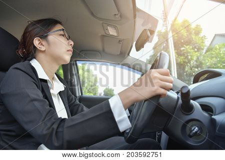 Tired Sleepy Asian glasses Business woman driving a car. Illness exhausted disease for overtime working concept.