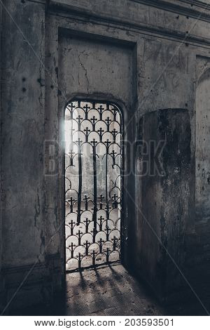 Door aperture with a rusty carved lattice in an old abandoned church or castle