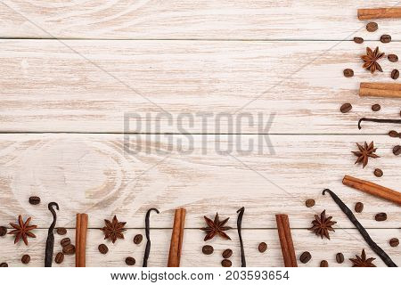 Frame of vanilla sticks, cinnamon, coffee beans and star anise on white wooden background with copy space for your text. Top view.