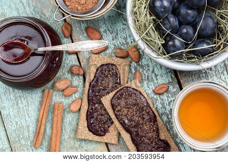 Healthy vegan snack. Rye crackers with homemade plum jam with raw cocoa beans tea cinnamon and fresh plums in hay on shabby green wooden table above view