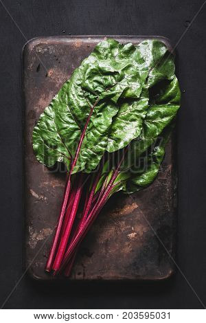 Fresh swiss chard leaves on dark rusty background. Table top view fresh organic green food