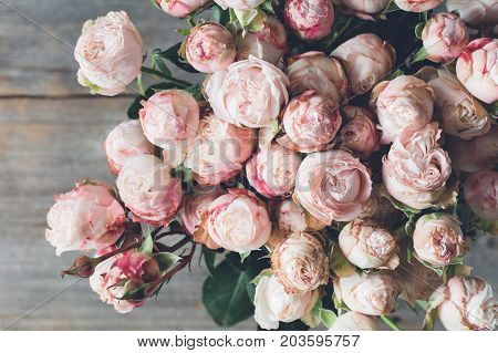 Pink shrub roses bouquet on wooden background. Beautiful wedding shabby chic bouquet of flowers. Closeup view. Vintage toning