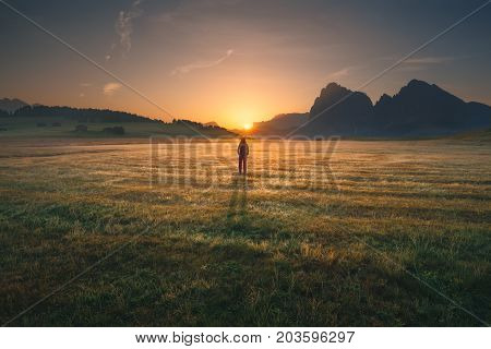 Young woman enjoying the beautiful illuminated nature while watching idyllic sunrise in Dolomites mountains. Lifestyle and freedom concept.