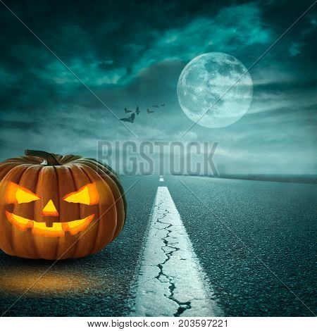 Lone scary pumpkin head jack lantern on the straight road towards full moon and bats in the clouds. Halloween holiday concept.