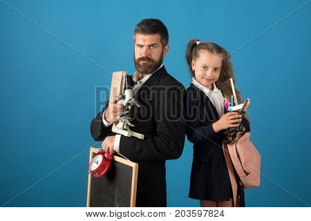 Teacher and schoolgirl with confident faces on blue background. Education and back to school concept. Kid and tutor hold microscope bag chalkboard clock and book. Man with beard and girl in uniform