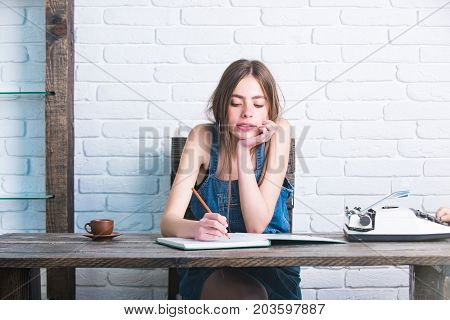 Girl writing with pencil in notebook. Young woman sitting at wooden table. Teenager student in jean pinafore on white brick wall. Study and learning concept. Education and knowledge