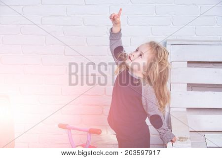 Child With Long Blond Hair On White Brick Wall