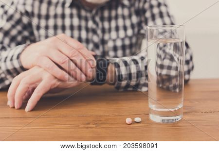 Taking pills. Unrecognizable senior man hands on table with glass of water and medicine. Healthcare, treatment, aging concept