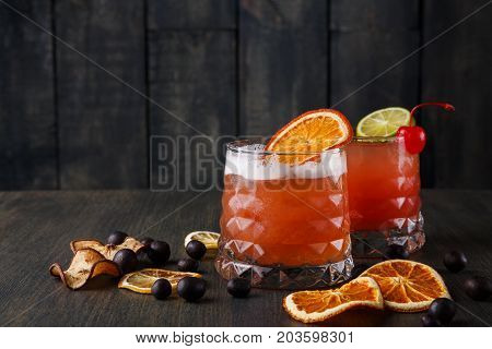 Cocktail on rustic wood background. Cold citrus alcohol beverage with tequila, blood orange juice and ginger beer, served with ice, citrons and chocolate snacks, copy space