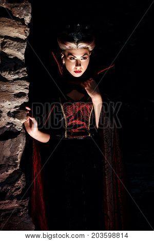 Evil Queen With A Crown In A Fantastic Portrait - Beautiful Mystical Princess In A Dark Cape Dracula