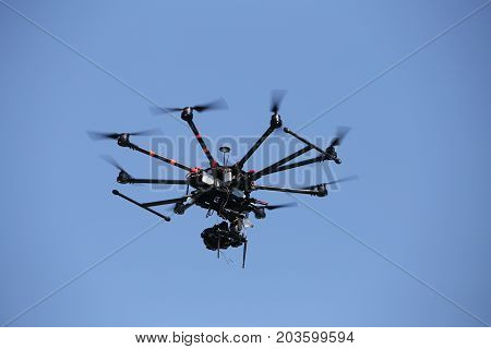 Black hexacopter octocopter is flying in sky