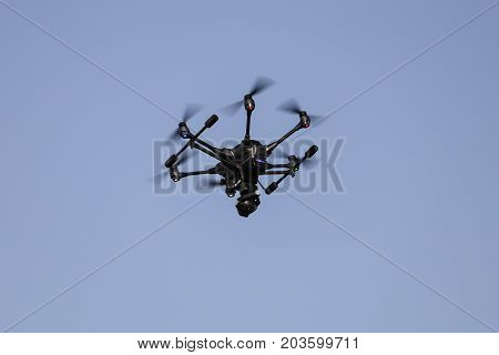 Black hexacopter helicopter is flying in sky