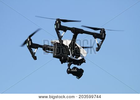 Black quadcopter helicopter is flying in sky
