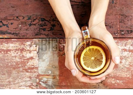 Copy space. The cup of hot tea with lemon. Hands. The concept of drinks lifestyle.
