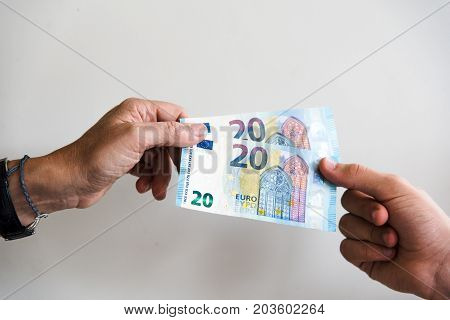 Hand of woman is giving euro money to a young man against white background