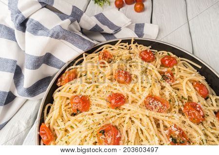 Spaghetti pasta with tomatoes and parsley on wooden table.