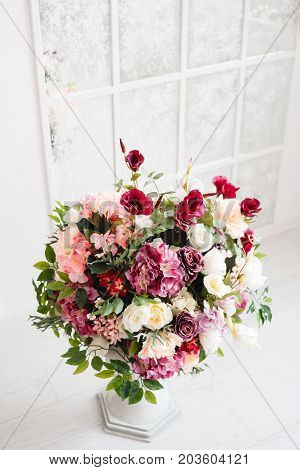 Magnificent bouquet of flowers in white vase. Indoor decoration, gallery, photo studios. Beautiful cream and dark-violet roses, deep red eustoma, purple hydrangea, free space