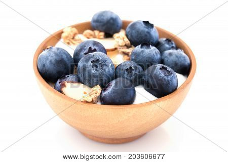 Yogurt with granola and organic blueberries in wooden bowl on white background.