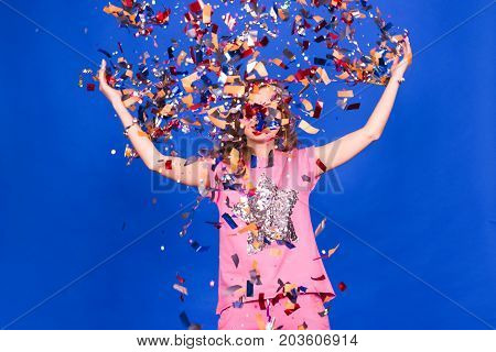 Beautiful happy woman at celebration party with confetti falling everywhere on her. Birthday or New Year eve celebrating concept.