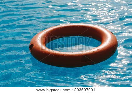 Orange lifebuoy in the blue water. Photo in the daytime.