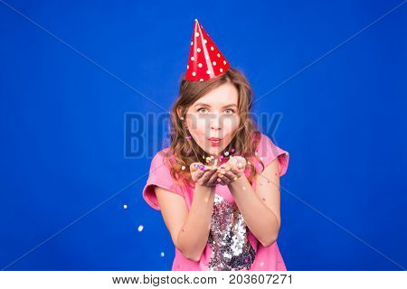 Pretty glamorous woman welcoming the new year 2018 blowing confetti into camera, photo booth style image.