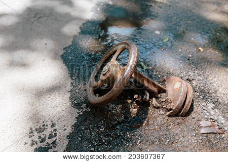 Old rusty water pressure tap buried in asphalt. Photo in the daytime.