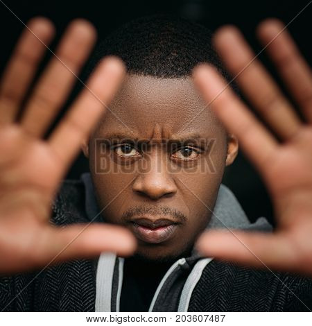 Black male with stop gesture in selective focus. Angry African American man on dark background, facial expression, emotional photo, protection concept