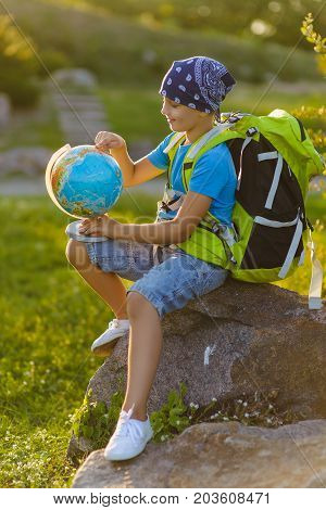 Teenager travelers with backpacks sitting on rock. Wanderlust travel concept.