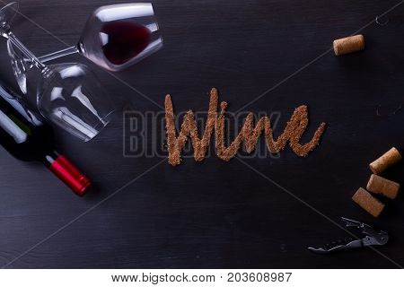 Bottle of red wine and two wine glasses on table with wine word letters
