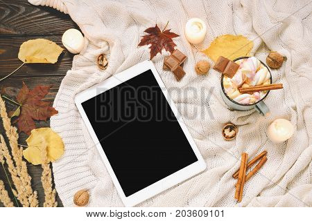 Autumn frame made of dried fall leaves, mug of cocoa with marshmellows, nuts, cinnamon, plaid, apples with tablet mock up. Top view on brown wood background. flat lay, copy space