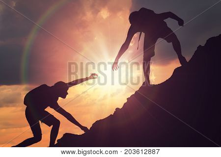Man Is Giving Helping Hand. Silhouettes Of People Climbing On Mo
