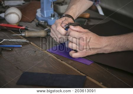 Leather maker cut leather with utility knife on wooden working table with instrument. Neat cutting leather product in workshop. Work with dangerous tool
