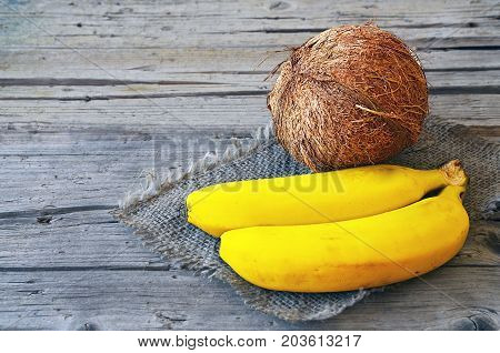 Bunch of ripe organic bananas and coconut on wooden background.Coconut and bananas.Banana coconut.Healthy eating,raw food or diet concept.Selective focus.