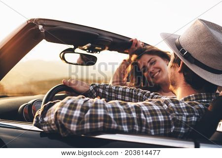 Loving Couple Of Hipsters In Cabriolet Car Enjoy View At Sunset. Man In Hat And Passenger Woman Look
