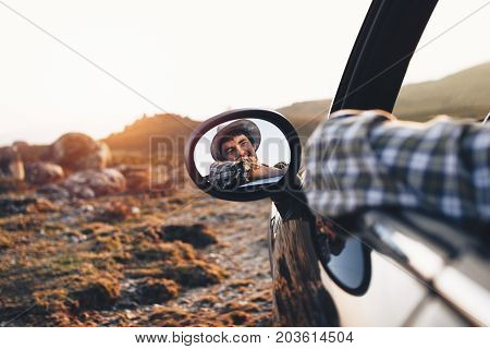 Trendy Man In Hat Sits On Convertible Car And Enjoy View At Sunset In Mountains. Hipster In Casual C