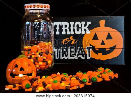 A candle burns in the jack-o-lantern while some candy corn is poured out on the table and some remains in the glass jar.